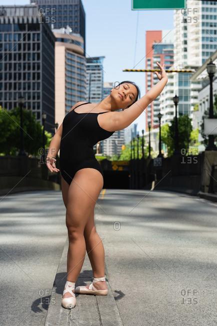 Beautiful female ballet dancer dancing on the street
