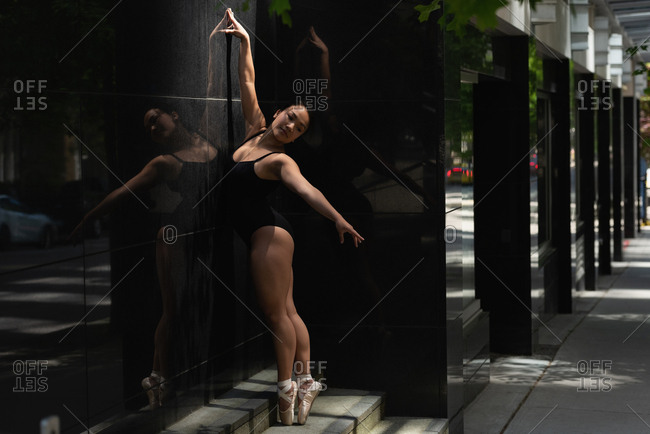 Beautiful female ballet dancer dancing on the sidewalk