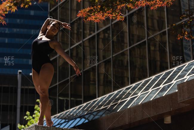 Beautiful female ballet dancer dancing in the city
