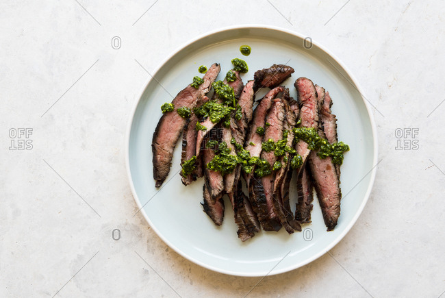 White plate with slices of flank steak with chimichurri sauce