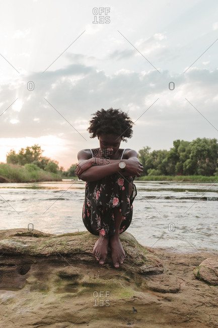 African American young girl sitting and relaxing on a rock formation in the middle of a river sunset background