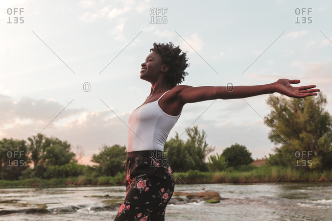 Side view of young African American girl opening her arms in freedom in a sunset