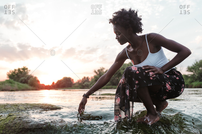 Side view of African American girl touching the water in a river sunset background