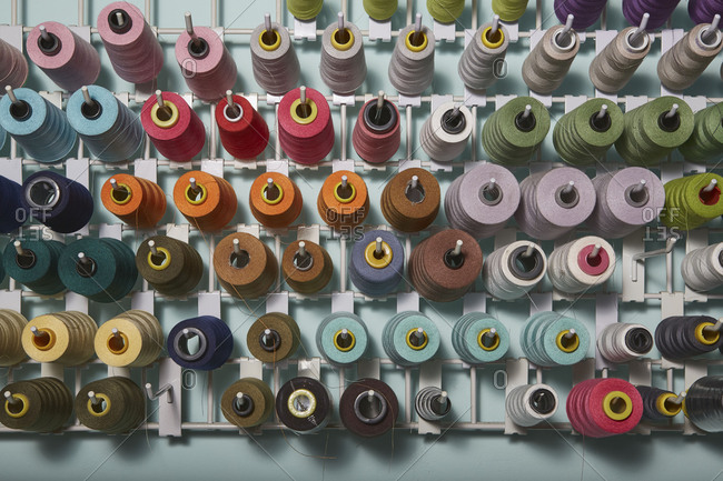 Colorful spools of thread arranged on a rack