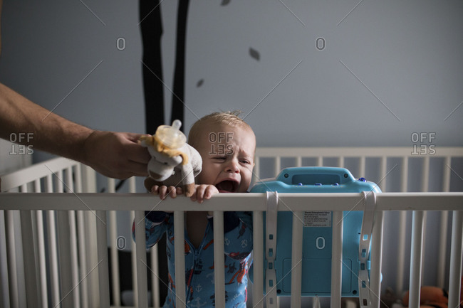 Father handing baby a pacifier while he cries in his crib