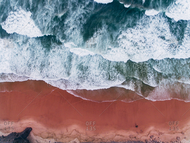 Aerial view of waves crashing onto beach with red sand