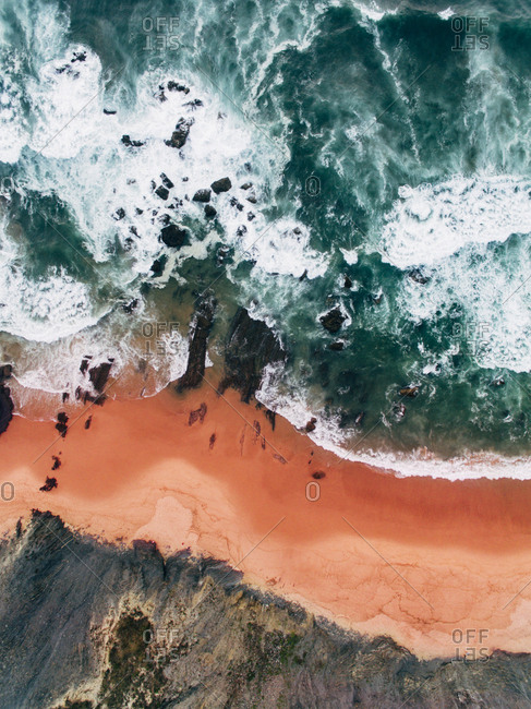 Aerial view of waves crashing onto rocks at beach with red sand