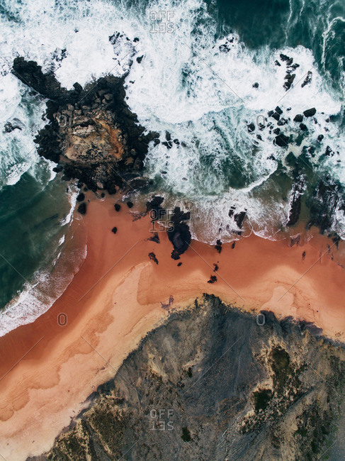 Aerial view of coastal rock formations at beach with red sand