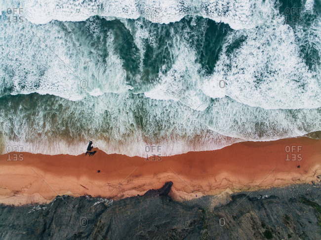 Aerial view of waves rolling onto beach with red sand