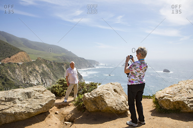 Monterey County, California, USA - April 22, 2018: Senior woman taking picture of man at scenic overlook along Highway 1 on the Bur Sur coast of California