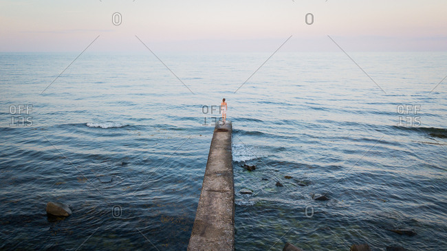 Woman standing at edge of jetty looking out over the ocean