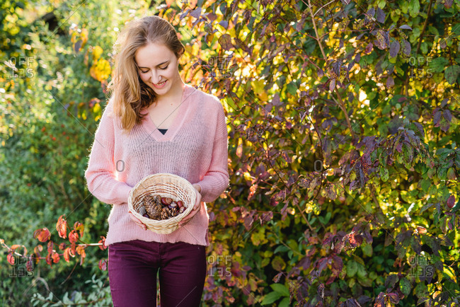 Garden, Young woman with basket collecting natural materials,