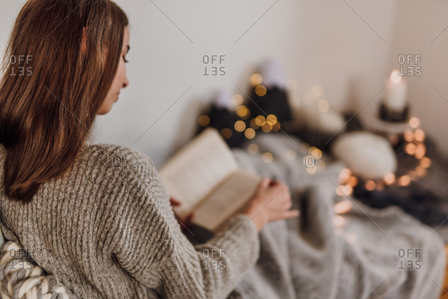 Young woman reading a book, cozy atmosphere