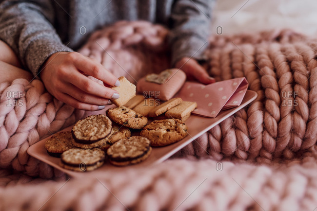 Young woman sitting in bed with a plate full of cookies, detail,
