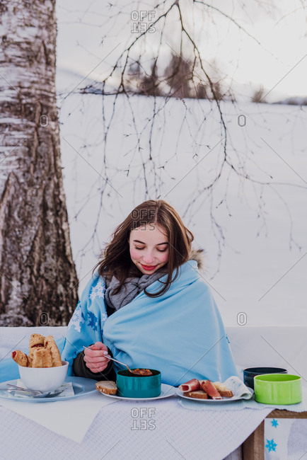 wintertime, Young woman wrapped in a blanket eats outside