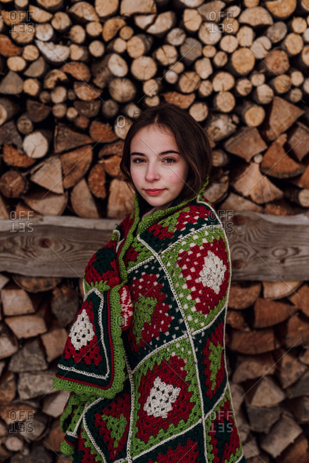 Young woman wrapped in a blanket in front of a woodpile, portrait