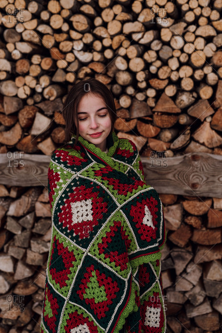 Young woman wrapped in a blanket in front of a woodpile