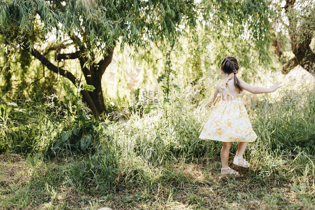Brunette girl in yellow floral dress twirling under willow trees