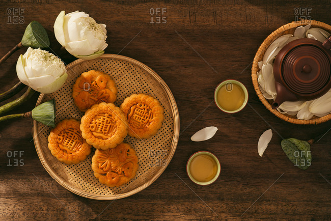 Vietnamese sweet food for mid autumn festival when full moon, moon cake from top view on black wooden background, delicious homemade mooncake of Vietnam cuisine culture