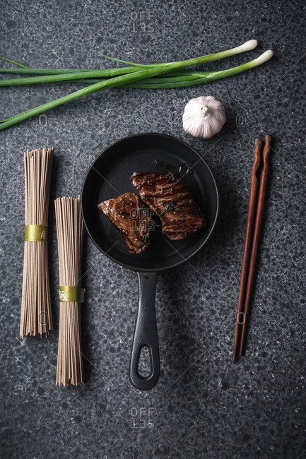 Ingredients for cooking soba with fried beef recipe. Flat lay on dark background