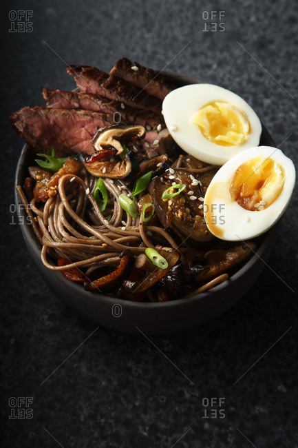 Close up image of soba noodles with sliced roasted beef, shiitake mushrooms, boiled eggs and fried vegetables in a bowl. Dark food photography