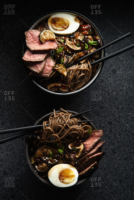Soba noodles with sliced roasted beef, shiitake mushrooms, boiled eggs and fried vegetables in a bowl. Dark food photography. Top view