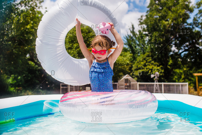 Little girl in backyard pool with inflatable rings
