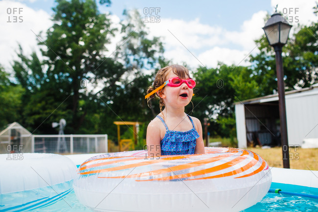Young girl in backyard pool with inflatable rings