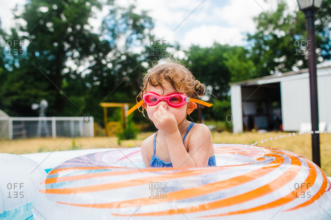 Little girl plugging nose in backyard pool with inflatable rings