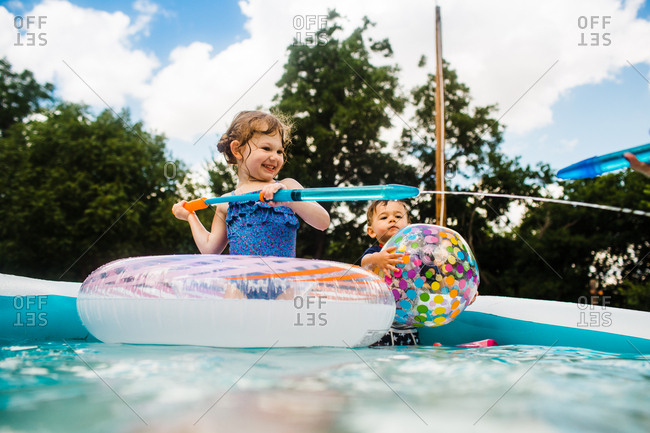 Young kids in backyard pool playing with a water squirter and beach ball