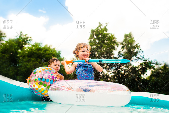 Two kids in backyard pool playing with a water squirter and beach ball