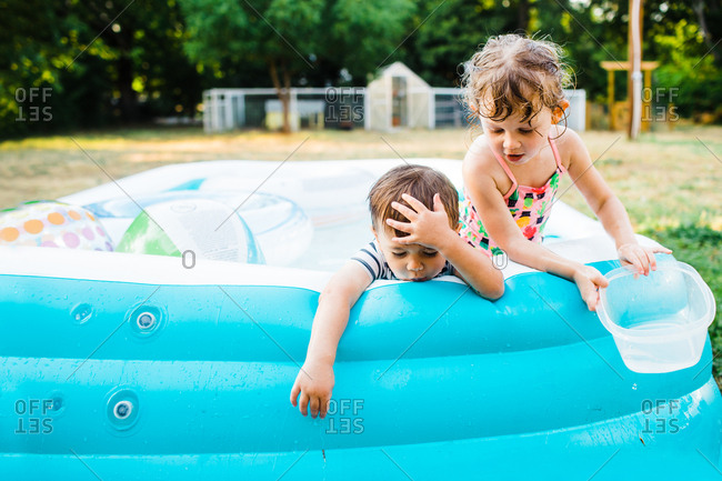 Two kids playing in a backyard swimming pool