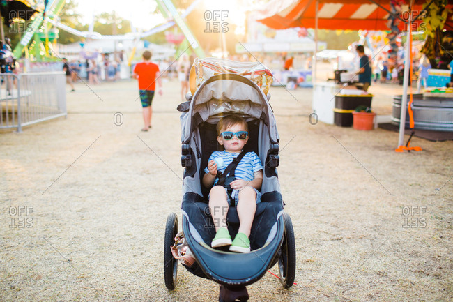 Toddler sitting in stroller at fair eating cotton candy