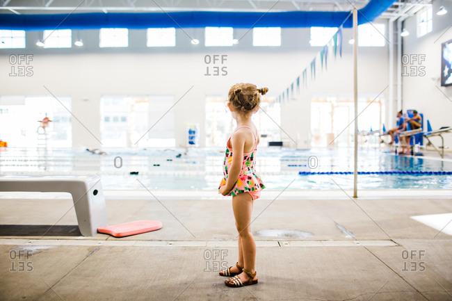 Girl standing by indoor swimming pool looking away