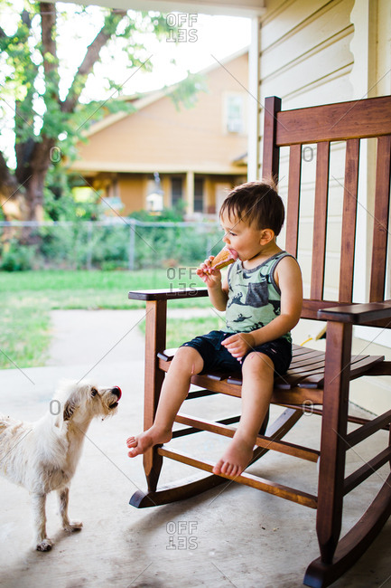 Dog watching little boy eat an ice cream cone on a rocking chair