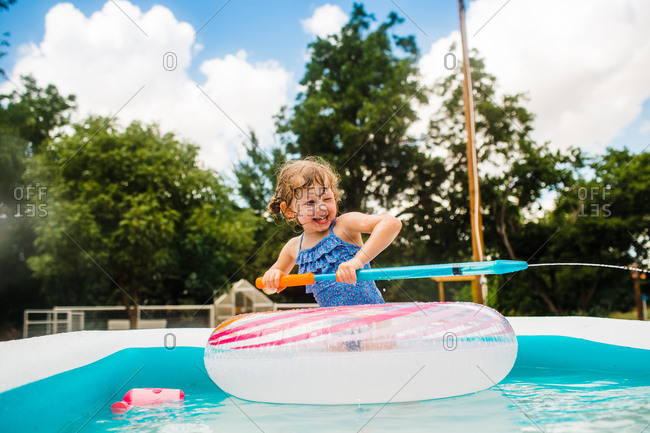 Little girl in backyard pool spraying with a water squirter
