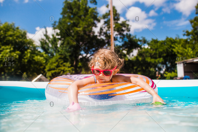 Little girl wearing sunglasses in backyard pool floating in a ring