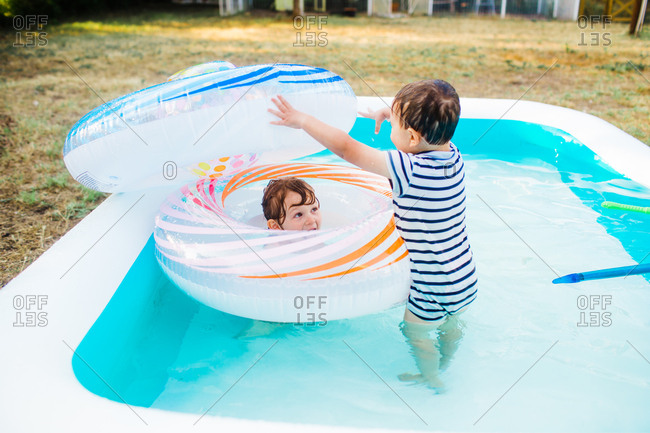 Two kids playing with inflatable rings in a backyard swimming pool
