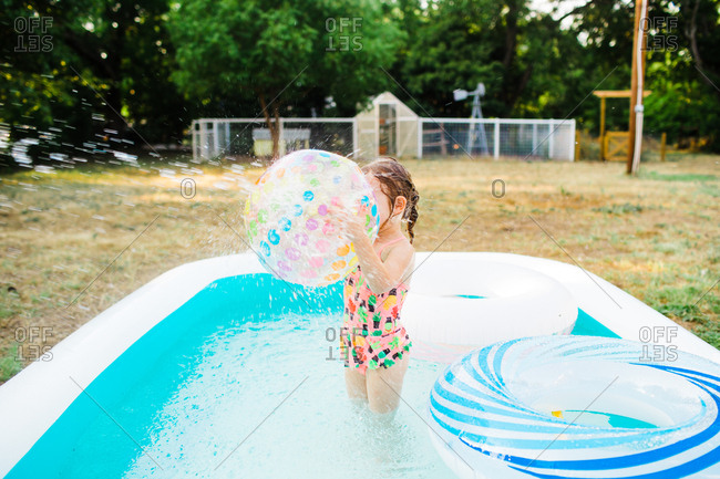 Little girl holding a beach ball in a backyard pool