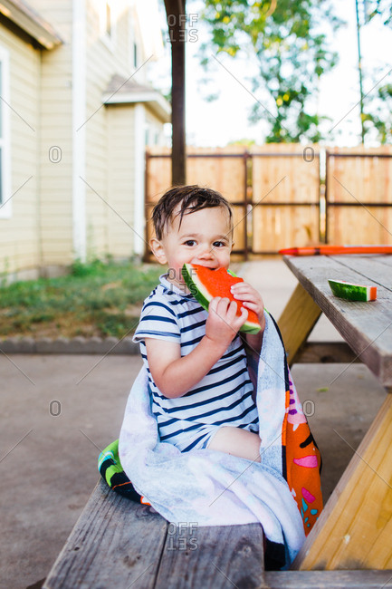 Little boy drying off with towel while eating watermelon