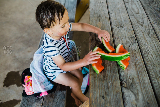 Toddler boy drying off with towel while eating watermelon