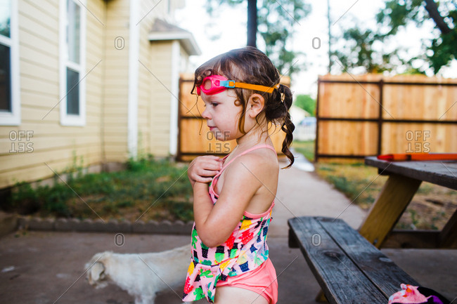 Girl standing by picnic table wearing goggles after swimming