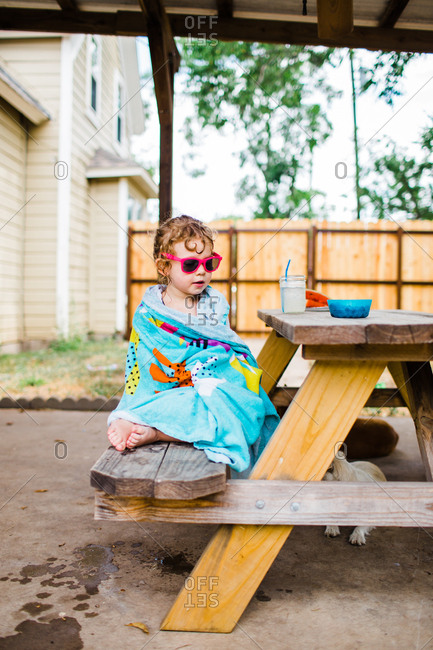 Young girl sitting on picnic table drying off with towel