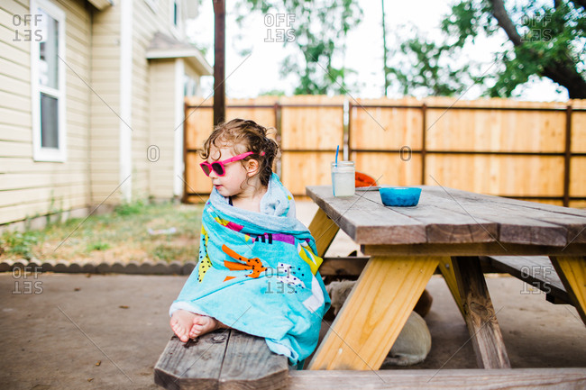 Little girl sitting on picnic table drying off with towel
