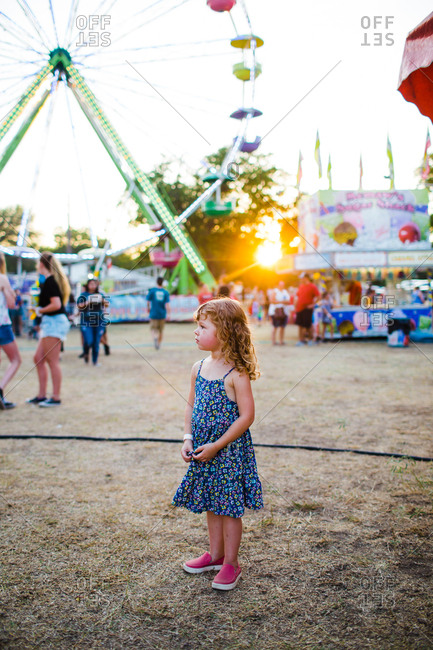 Young girl standing by big wheel at a fair at sunset