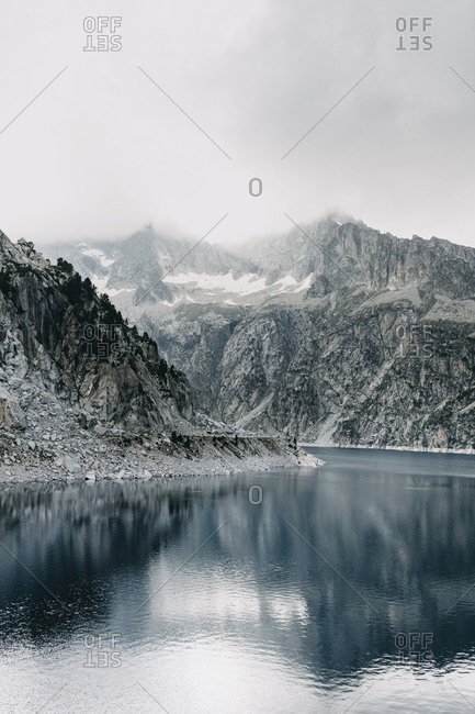 Snow falling on mountain and lake in France
