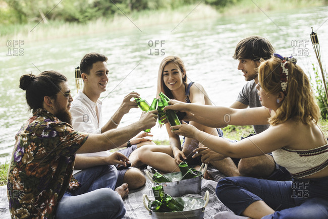 Group of friends sitting together on the shore of a lake drinking beer and smoking