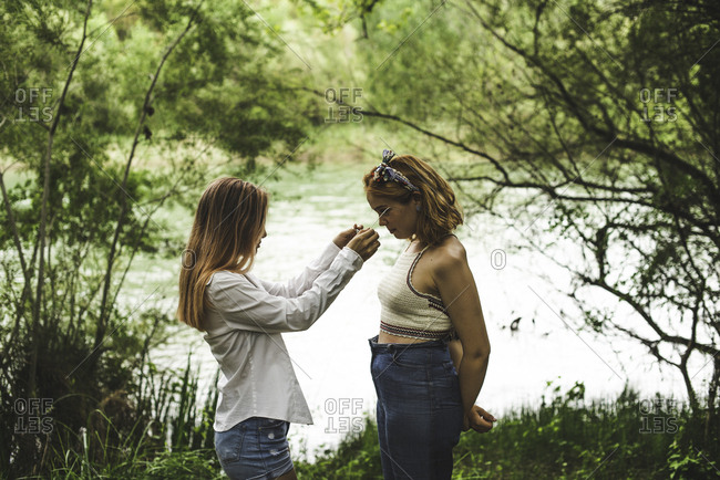 Young woman putting glasses on her friend