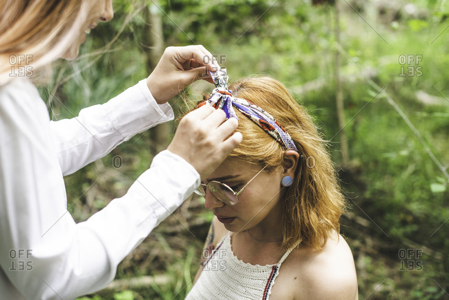 Young woman tying a bow in headband on her friend's head