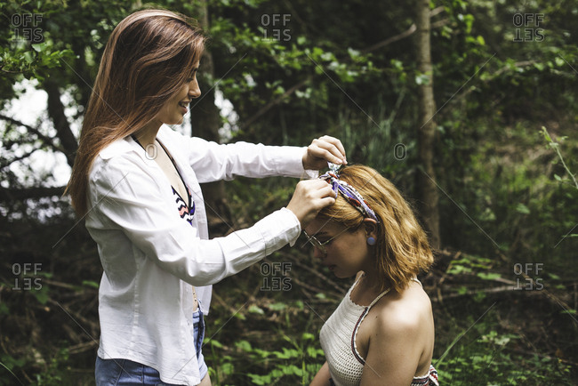 Young woman tying a bow in her friend's headband